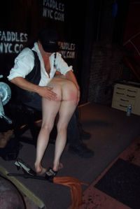 Spanking a brat at Paddles Night Club.